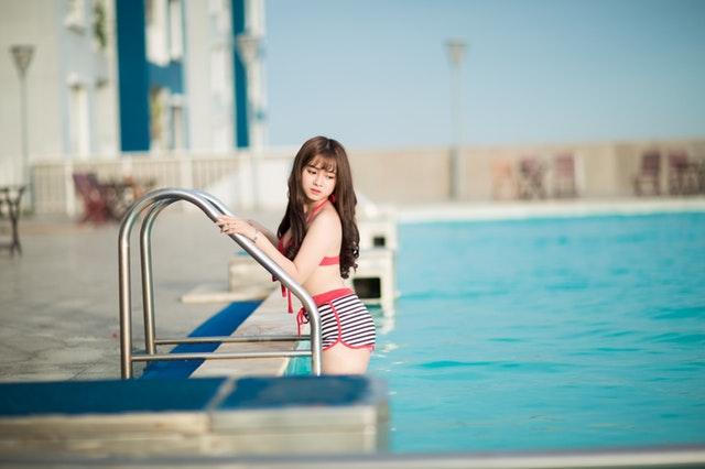 žena vylézající z bazénu po schůdkách
